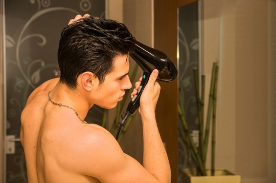 Shirtless young man drying hair with hairdryer, looking at camera at home