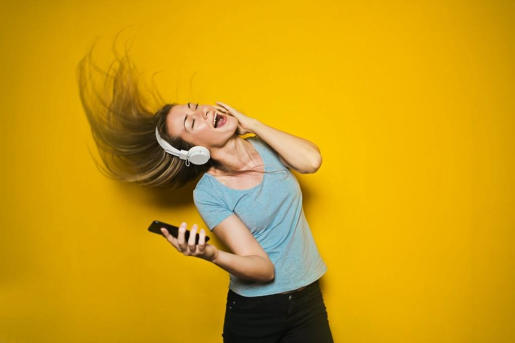 woman waving her hair in the beat of the music on her headphone