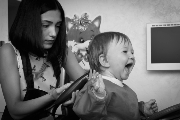 mother cutting boy haircuts at home