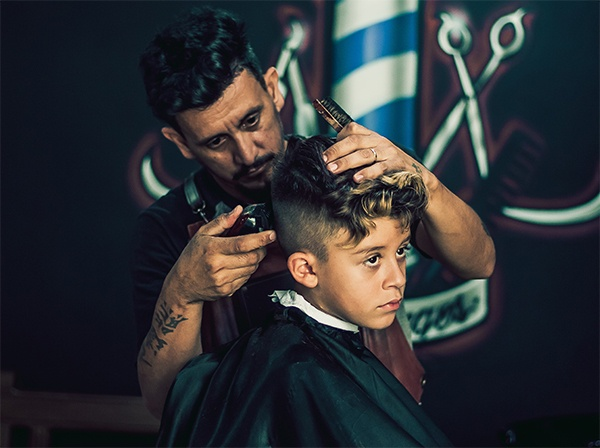 barber cutting hair of a kid